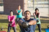 stock photo of kettles  - Four people exercising in outdoor boot camp with kettle bells - JPG