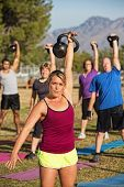 stock photo of boot camp  - Athletic woman teaching boot camp fitness class outdoors - JPG