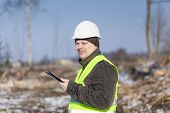 Lumberjack with tablet PC in cleared forest in winter