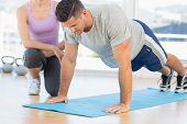 stock photo of personal assistant  - Female trainer assisting man with push ups at gym - JPG