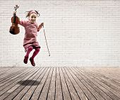 foto of violin  - little girl with violin jumping on a room with white bricks wall and wood floor - JPG