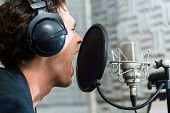 pic of recording studio  - Young male singer or musician with microphone and headphone for audio recording in the Studio - JPG