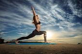 picture of strength  - Woman practicing Warrior yoga pose outdoors over sunset sky background - JPG