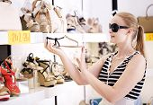 pic of peep toe  - Young woman in sunglasses choosing summer shoes in the shop - JPG