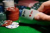 stock photo of poker hand  - Chips and cards for poker in hand on green table - JPG