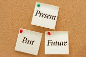 picture of past future  - The past present and the future Three yellow sticky notes on a cork board with the words Past Present and Future - JPG