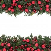 stock photo of greenery  - Christmas background  border with red bauble decoration with holly and winter greenery over white - JPG