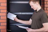 picture of postman  - Young friendly postman giving person the letter - JPG
