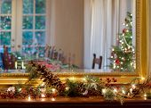 picture of cozy hearth  - A table set for Christmas eve family dinner can be seen reflected in a mirror hanging about a hearth decorated with pine cones and twinkling lights.