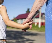 stock photo of grandmother  - Hands of grandmother and child - JPG