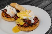 picture of benediction  - Benedict eggs with crispy bacon and hollandaise sauce on toasted Maffin on clean plate - JPG