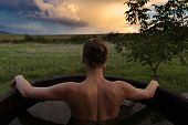 foto of bathing  - Bathing woman relaxing in outdoor bath or tub and watching sunset - JPG