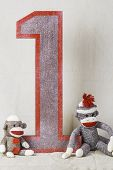 stock photo of sock-monkey  - Sock monkeys sitting around a wooden number one sign - JPG