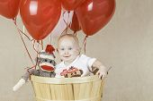pic of sock-monkey  - An infant boy sitting in a wooden basket with balloons and a sock monkey - JPG