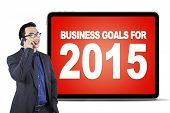 stock photo of motivation talk  - Young entrepreneur talking on the cellphone in front of a board of business goals for 2015 - JPG
