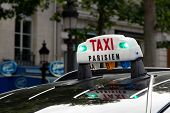 foto of cabs  - The Taxi sign on top of the roof of the cab in Paris - JPG