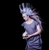 foto of evil  - dark fashion shot of a woman holding a evil skull crazy hairstyle with feathers - JPG