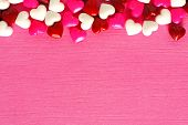 picture of valentine candy  - Valentines Day candy top border on a pink paper background - JPG