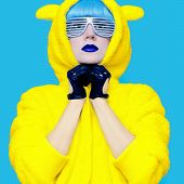 foto of exclusive  - Teddy bear crazy girl in a bright hoodie on a blue background color exclusive - JPG