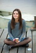 stock photo of jeans skirt  - Young beautful brunette woman in blouse and denim skirt sitting on the river pier with coffee and her smartphone - JPG