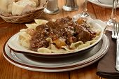picture of boeuf  - Boeuf Bourguignon on farfalle pasta with a basket of dinner rolls - JPG