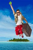 stock photo of stereotype  - a young attractive male in a colorful outfit in a tropical island setting as a stereotype tourist - JPG