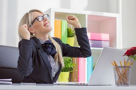 stock photo of self-employment  - Happy young business woman enjoying success at work - JPG