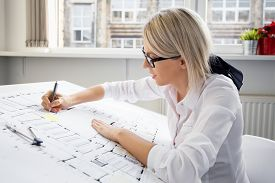 image of draft  - Young female architect working on architectural blueprint - JPG