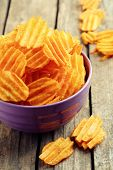 pic of potato chips  - Delicious potato chips in bowl on wooden table close - JPG