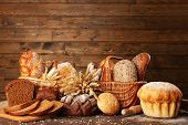 picture of wooden basket  - Different bread with ears in basket on wooden background - JPG