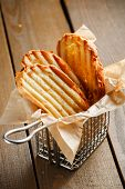 image of crust  - Toasted slices of bread with a golden crust neatly stacked in a metal stand on a wooden brown background - JPG