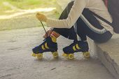 stock photo of roller-skating  - Woman Ties LAces on Vintage Retro Quad Roller Skates Sitting on Concreet Block in Urban Environment Toned Image - JPG