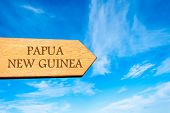 picture of papua new guinea  - Wooden arrow sign pointing destination PAPUA NEW GUINEA against clear blue sky with copy space available - JPG