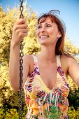 stock photo of swing  - happy female swings on sunny day - JPG