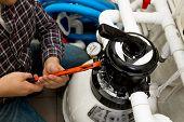 foto of manometer  - Closeup shot of handyman installing manometer on high pressure system - JPG