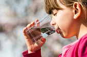 foto of environmental protection  - Young girl holding glass and drinking pure water - JPG