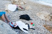 foto of pacifier  - Sleeping baby with a pacifier lying on a pebbled beach in improvised bed during a family vacation - JPG