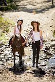 picture of horse-riders  - cute female kid jockey having fun learning riding pony outdoors happy with young Australian American horse instructor woman in cowboy look teaching the little rider in summer nature countryside - JPG