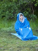 picture of sleeping bag  - The man is resting in a sleeping bag on the background of green forest - JPG