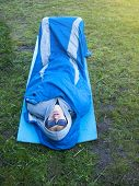 image of sleeping bag  - The man is resting in a sleeping bag on a background of green grass.