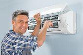 stock photo of air compressor  - Portrait Of A Happy Male Technician Repairing Air Conditioner - JPG