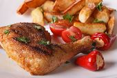 picture of thighs  - Grilled chicken thighs fried potatoes and vegetables on a plate macro - JPG