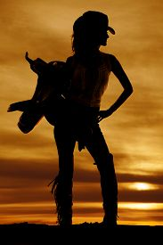 image of western saddle  - A silhouette of a woman in her western wear holding on to her saddle - JPG