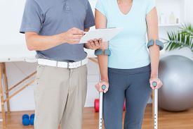 picture of crutch  - Woman using crutch and talking with her doctor in medical office - JPG