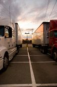 pic of semi-truck  - two trucks side by side on a sunset background