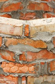 stock photo of mortar-joint  - A fragment of brick wall under construction at home - JPG