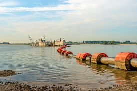 foto of floating  - Suction dredger in a Dutch river sucks sand and gravel from the river bottom and transports it via a floating pipeline with orange floats to the shore - JPG