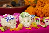 image of mexican food  - Mexican offering for the dead showing sugar skulls and assorted traditional candy - JPG