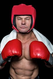 picture of headgear  - Confident boxer with gloves and headgear against black background - JPG