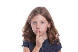 stock photo of shhh  - A cute little girl holds her finger over her mouth to shush - JPG